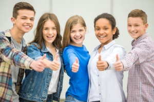 a group of teenagers showing thumbs up