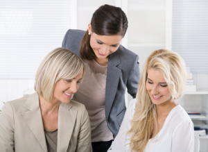Successful team of smiling businesswoman sitting at desk